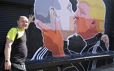 Restaurant owner Dominykas Ceckauskas poses next to a mural on the wall of his establishment depicting US  Presidential hopeful Donald Trump and Russian President Vladimir Putin greeting each other with a kiss in the Lithuanian capital Vilnius on May 13, 2016 (AFP/Petras Malukas)