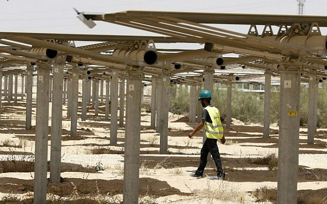 A worker walks past some of the 55,000 mirrors directing sunlight toward the Ashalim solar tower, which is under construction near the southern Israeli kibbutz of Ashalim in the Negev desert, May 26, 2016. (Jack Guez/AFP)