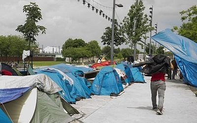 Refugees and migrants are pictured in a makeshift camp in Paris on May 27, 2016. (AFP/ JOEL SAGET)