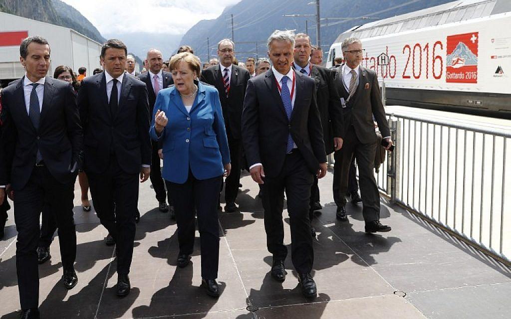 German Chancellor Angela Merkel, center, speaks with Austrian Chancellor Christian Kern, left, Italian Prime Minister Matteo Renzi, second left, and Swiss Federal Councillor Didier Burkhalter, second right, on the opening day of the Gotthard Rail Tunnel in Erstfeld on June 1, 2016. (AFP/Peter Klaunzer/Pool)