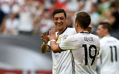 German player Mesut Ozil, left, and Mario Goetze celebrate after Goetze's goal vie during the UEFA EURO 2016 friendly football match Germany vs. Hungary at the Veltins Arena in Gelsenkirchen, western Germany, on June 4, 2016. (Patrik Stollarz/AFP)