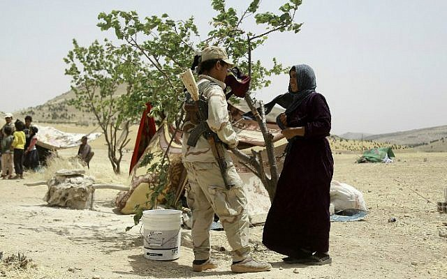 A Syrian woman who fled the assault launched by Arab and Kurdish forces against Islamic State (IS) fighters in the town of Manbij talks to a Kurdish fighter upon her arrival at an encampment on the outskirts of the town, June 4, 2016. (Delil Souleiman/AFP)