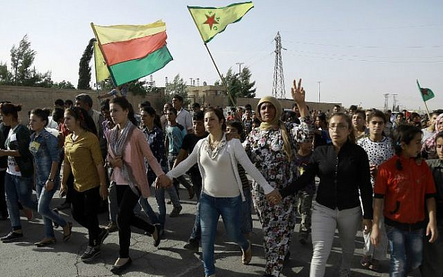 Syrian Kurds march during the funeral of fighters who died during an assault launched by Arab and Kurdish forces against the Islamic State (IS) group in the town of Manbij, in the Syrian Kurdish town of Kobane on June 4, 2016. (Delil Souleiman/AFP)
