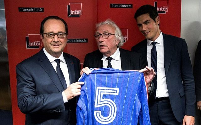 French President Francois Hollande poses after receiving the jersey of former French soccer player Marius Tresor following the France Inter's radio program 'L'Oeil du Tigre' (The Eye of the Tiger) at the Radio France headquarters in Paris, June 5, 2016. (AFP Photo/Pool/Etienne Laurent)