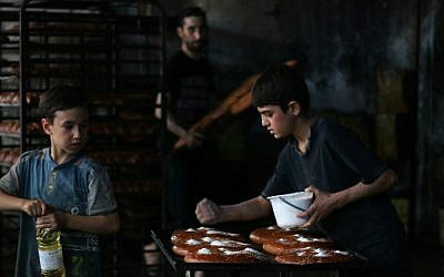 Syrian children help to prepare bread at a bakery in the rebel-held side of the northern city of Aleppo on June 6, 2016, as Muslims get ready for Iftar, or breaking of the daylong fast, on the first day of the holy month of Ramadan. (Thaer Mohammed/AFP)