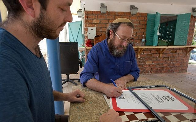 Rabi Aaron Leibowitz (C), the founder of Hashgach Pratit - Hebrew for private supervision -, which checks if restaurants abide by kosher practices, signs a certificate for the new bar Eitan Steinberg in the center of Jerusalem on June 8, 2016.(AFP PHOTO / MENAHEM KAHANA)
