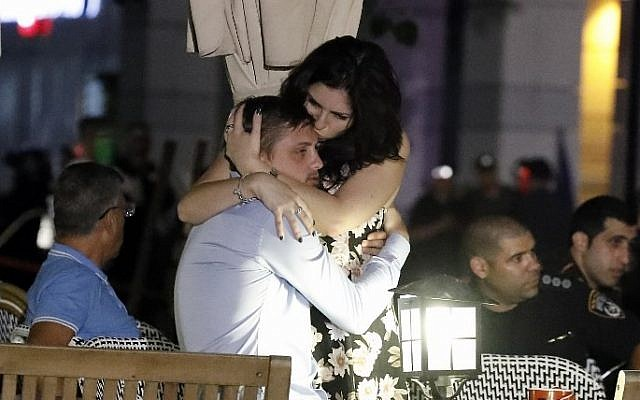 Israelis embrace following a shooting attack at a shopping complex in the Mediterranean coastal city of Tel Aviv on June 8, 2016. (AFP PHOTO / JACK GUEZ)