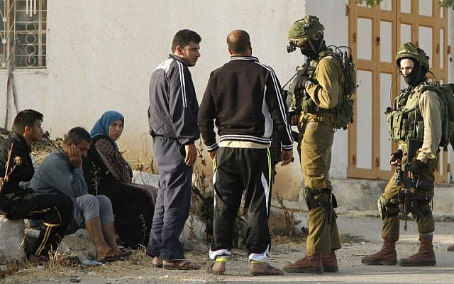 Israeli soldiers talk to Palestinians after the army entered the village of Yatta in the West Bank on June 9,2016.  (AFP PHOTO / HAZEM BADER)
