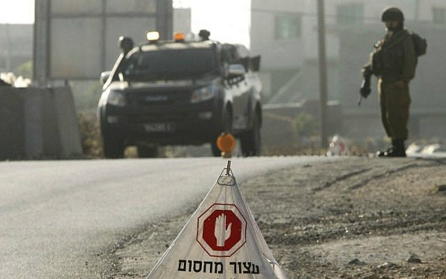 IDF soldiers man a temporary checkpoint at the entrance to the Palestinian village of Yatta in the southern West Bank on June 9, 2016 after the army entered the village in search of clues related to a shooting attack the previous night in Tel Aviv in which four people were killed and 16 others wounded. (Hazem Bader/AFP)