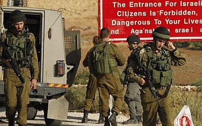 Soldiers are seen at one of the entrances of the Palestinian village of Yatta, near Hebron, on June 9, 2016 (AFP/Hazem Bader)