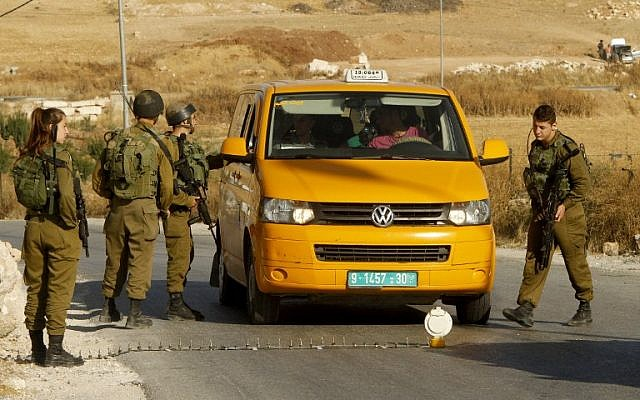 Israeli soldiers man a temporary checkpoint at the entrance of the Palestinian town of Yatta in the West Bank on June 9,2016. (AFP/HAZEM BADE)