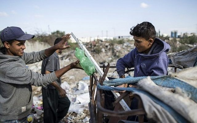 Palestinian Karam al-Zaaneen (R), 13, and his brother Mustafa, 16, collect plastic at a garbage dump in Beit Hanun in the northern Gaza Strip on May 18, 2016. (AFP PHOTO / MAHMUD HAMS)