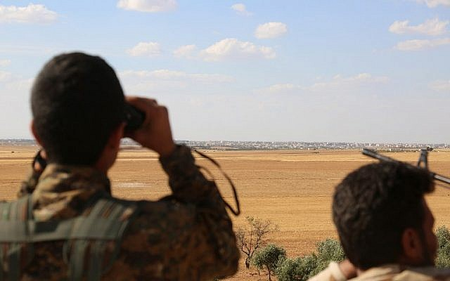 Fighters from the Syrian Democratic Forces use binoculars from a viewpoint overlooking the northern Syrian town of Manbij held by the Islamic State group as they encircle the town cutting off the jihadists' main supply route between Syria and Turkey on June 10, 2016. (AFP PHOTO/DELIL SOULEIMAN)