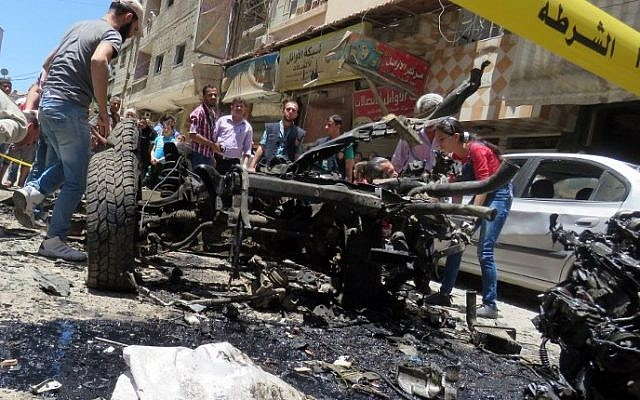 Syrians look at a burnt out vehicle used in a double bombing attack on June 11, 2016 outside the Sayeda Zeinab shrine, which is revered by Shiites around the world, some ten kilometers south of the center of Damascus, in the latest in repeated deadly strikes on the revered site. (AFP)