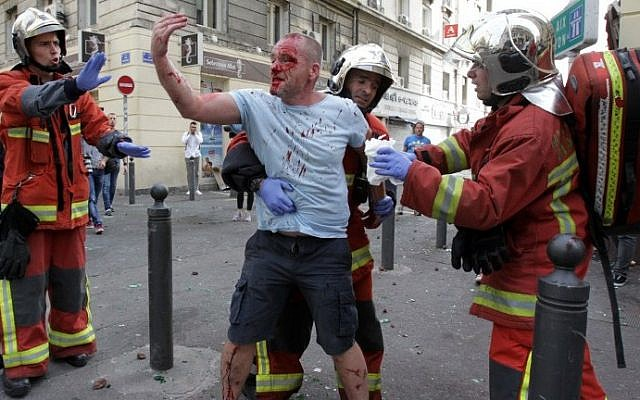 An injured English supporter is helped by a rescue team after a street brawl ahead of the England-Russia Euro 2016 soccer match om Marseille on June 11, 2016. (AFP PHOTO/JEAN CHRISTOPHE MAGNENET)
