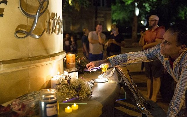 Mourners light candles at the Legacy of Love statue during a vigil in Dallas, Texas, on June 12, 2016, for victims of the attack at Orlando's Pulse Nightclub in Orlando, Florida. (AFP/Laura Buckman)