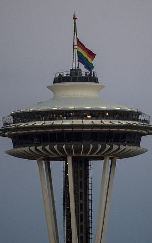 A rainbow flag flies at half mast on the Space Needle in Seattle, Washington on June 12, 2016, in honor of the victims of the nightclub shooting in Orlando.(AFP PHOTO / OMAR TORRES)