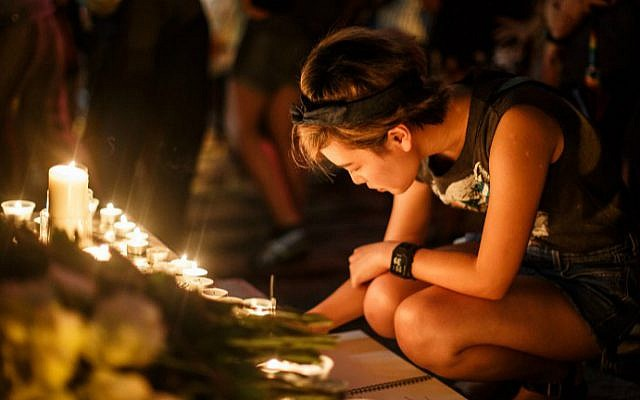 A woman in Hong Kong writes a message of support in a book placed in front of candles left by other attendees of a vigil for the victims of the Orlando shooting in Florida, June 13, 2016. (Anthony Wallace/AFP)