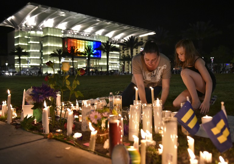 A woman and child arrange candles for the victims of the Pulse nightclub shooting. (AFP PHOTO / MANDEL NGAN)