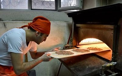 A picture taken on March 31, 2016 shows Kaits Jabakhchuryan, who came from Aleppo in 2012, baking lahmajoon -- a thin, crusty bread topped with ground meat -- at his restaurant in Yerevan. (AFP PHOTO / KAREN MINASYAN)