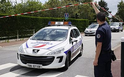 A photo taken on June 14, 2016 in Magnanville, shows a French police officer lifting the cordon as a police vehicle leaves the street where a man claiming allegiance to the Islamic State group killed a French policeman and his partner on the night of June 13.(AFP/MATTHIEU ALEXANDRE)