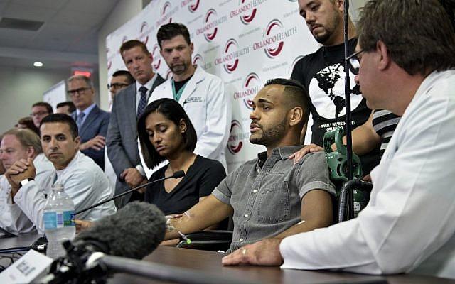 Angel Colon (3rd-R), a survivor of the Pulse nightclub mass shooting, speaks during a press conference with Orlando Health trauma staff at Orlando Regional Medical Center June 14, 2016 in Orlando, Florida. AFP PHOTO / Brendan Smialowski)