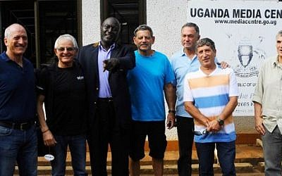 A picture taken on June 14, 2016 shows (LtoR) Eyal Oren, Shlomo Carmel, Jaffer Amin, Amjon Peled, Alex Davidi, unidentified, and Amir Ofer, members of the former IDF commandos and Entebbe hostages, posing in Kampala ahead of the 40th anniversary of their rescue. (AFP PHOTO / RONALD KABUUBI)