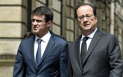 French Prime Minister Manuel Valls (L), and French President Francois Hollande (R), walk back to the Elysee palace on June 15, 2016, in Paris after a ceremony at the Ministry of Interior to pay a tribute to a French policeman and his partner, who were killed on June 13 by a man claiming allegiance to the Islamic State group. (AFP PHOTO / ALAIN JOCARD)