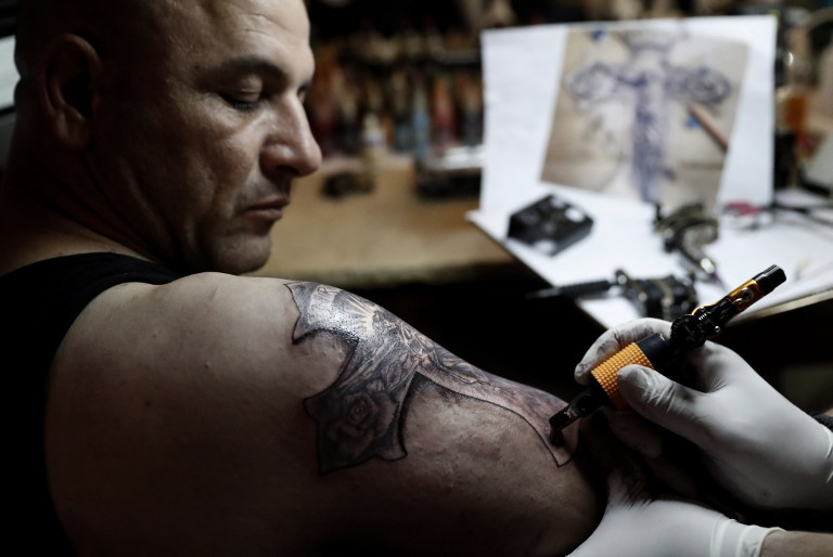 This photo taken on April 28, 2016 shows Christian Palestinian tattoo artist Walid Ayash (out of shot) drawing a tattoo depicting a crucified Jesus Christ on the arm of a Coptic Egyptian pilgrim, at his studio in the West Bank town of Bethlehem. (AFP PHOTO / THOMAS COEX)