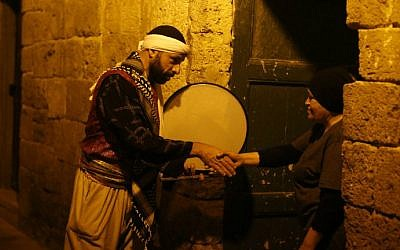 """Michel Ayoub, an Arab-Israeli Christian man carrying out the role of a """"musaharati,"""" the traditional figure who awakens Muslims for the """"suhur,"""" the pre-dawn traditional meal before Muslims start their fast during the sacred month of Ramadan, greets a woman in the street as he rouses Muslim residents in the northern Israeli port city of Acre on June 16, 2016. (Ahmad Gharabli/AFP)"""