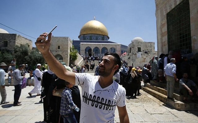 A Palestinian Muslim worshiper takes a selfie near the Dome of the Rock on the Temple Mount in Jerusalem on June 17, 2016, during Friday prayers in  the holy fasting month of Ramadan. (AFP Photo/Ahmad Gharabli)