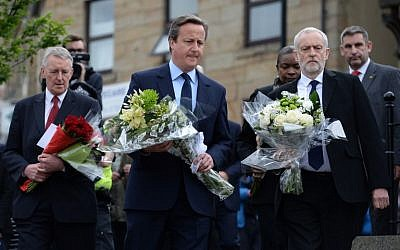 British Prime Minister David Cameron, center, Labour MP Hilary Benn left, and Labour Party leader Jeremy Corbyn, right, prepare to lay flowers in memory of slain Labour MP Jo Cox, in Birstall, northern England, on June 17, 2016. (AFP/OLI SCARFF)
