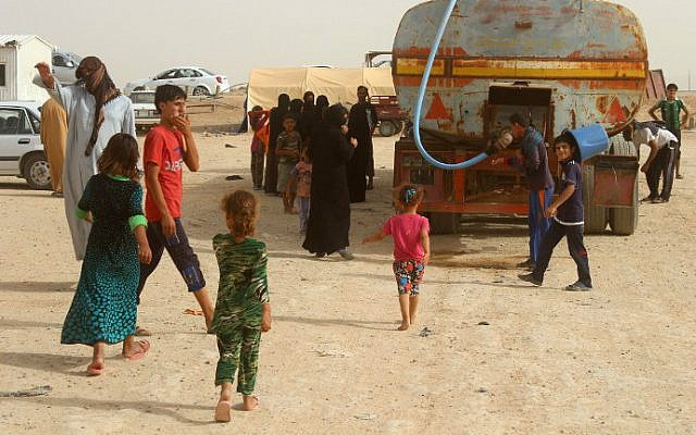 Displaced Iraqis from the embattled city of Fallujah wait for water to be delivered at a camp suffering from water and food shortages where they are taking shelter some 18 kilometers from Ramadi on June 18, 2016. (Moadh al-Dulaimi/AFP)