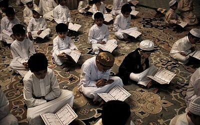 Bahraini Muslim boys read the Quran, Islam's holy book, during the holy fasting month of Ramadan at a mosque in the village of Sanabis, west of Manama, on June 18, 2016. (Mohammed al-Shaikh/AFP)
