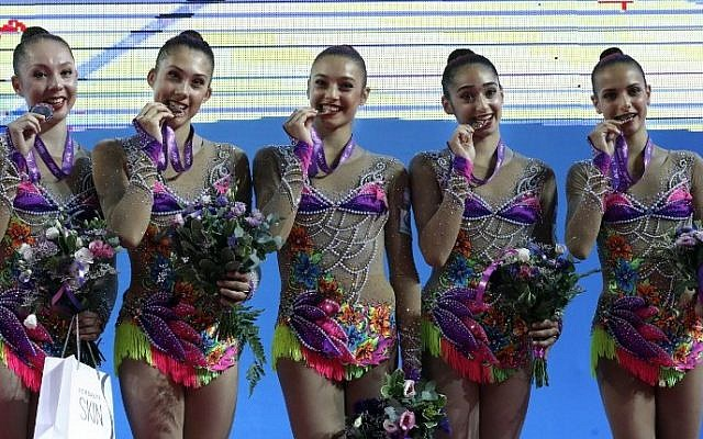 Israeli gymnasts team celebrate their gold medals on the podium after the Group Senior apparatus final - 3 pairs of clubs and 2 hoops during the 32nd Rhythmic Gymnastics European championships 2016 at the Holon Toto Hall in the Israeli city of Holon, on June 19, 2016. Israel won the gold medal, while Spain took the silver medal and Bulgaria won the bronze. (AFP/ THOMAS COEX)