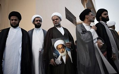 Bahraini Shiite clerics attend a protest against the revocation of the citizenship of top Bahraini Shiite cleric Sheikh Isa Qassim (portrait), near his house in the village of Diraz, west of the capital Manama,  June 20, 2016. (AFP/MOHAMMED AL-SHAIKH)