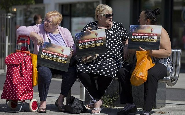 Leave supporters holds placards as they sit in Clacton-on-Sea as UK Independence Party (UKIP) leader Nigel Farage visits on June 21, 2016.(AFP PHOTO / JUSTIN TALLIS)