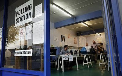 A woman collects her laundry before the polling station opens as a presiding officer and poll clerk set up a polling station in a laundromat in Headington outside Oxford on June 23, 2016. (AFP/ADRIAN DENNIS)