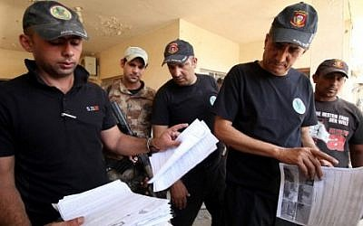 Members of the Iraqi counter-terrorism forces inspect documents in a building formerly used as a home-made bomb making factory by Islamic State (IS) group fighters in the northern Shurta neighbourhood of Fallujah as they patrol the city clearing roadside bombs and booby-traps on June 23, 2016. (AFP PHOTO / HAIDAR MOHAMMED ALI)