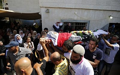 Mourners carry the body of 15-year-old Palestinian teenager Mahmoud Badran who was killed by Israeli troops on June 21, 2016, during his funeral in the village of Beit Ur-Tahta near the West Bank city of Ramallah on June 23, 2016. (AFP/Abbas Momani)