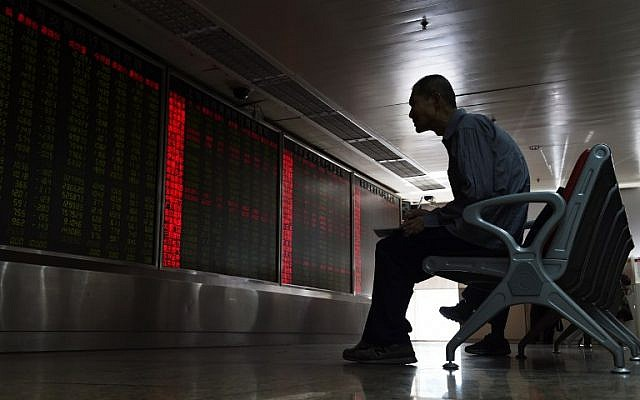 An investor watches stock price movements on a screen at a securities company in Beijing on June 24, 2016. (AFP PHOTO / GREG BAKER)