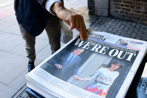 A man takes a copy of the London Evening Standard with the front page reporting the resignation of British Prime Minister David Cameron and the vote to leave the EU in a referendum, showing a pictured of Cameron holding hands with his wife Samantha as they come out from 10 Downing Street, in London on June 24, 2016. (AFP / LEON NEAL)