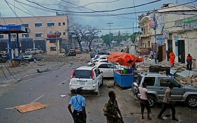 People and Somali security forces walk across the scene of a car bomb attack claimed by Al-Qaeda-affiliated Shabab militants which killed at least 5 people, on the Naasa Hablood hotel in Mogadishu on June 25, 2016. (AFP PHOTO / MOHAMED ABDIWAHAB)