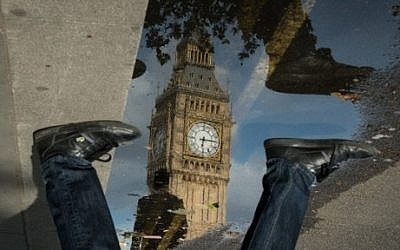 The Queen Elizabeth Tower (Big Ben) is reflected in a puddle as a man walks by in London, on 27 June 2016. (AFP PHOTO / Leon NEAL)