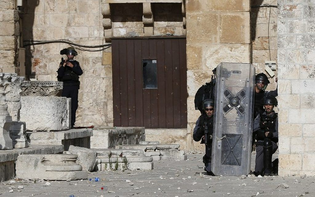 Israeli police take cover as Palestinian protesters throw stones at them at Jerusalem's Temple Mount compound during clashes between Israeli police and Muslims for the third consecutive day on June 28, 2016 in Jerusalem's Old City. (AFP/AHMAD GHARABLI)