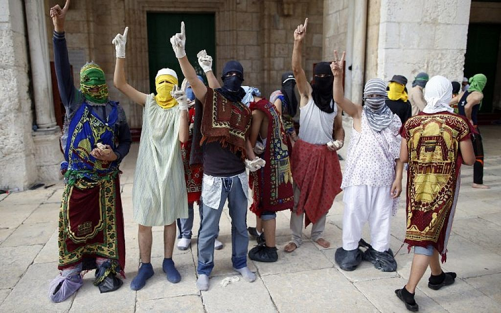 Masked Palestinian protesters wearing pieces of cloth around their bodies gesture during clashes with the Israeli police at Jerusalem's Temple Mount compound for the thrid consecutive day on June 28, 2016. (AFP/AHMAD GHARABLI)