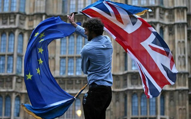 Illustrative: A man waves both a Union flag and a European flag together on College Green outside the UK Parliament on June 28, 2016. (Justin Tallis/AFP)