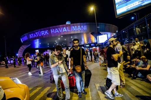 Passengers leave Ataturk airport in Istanbul on June 28, 2016 after two explosions followed by gunfire hit Turkey's biggest airport, killing at least 28 people and injuring 20. / AFP PHOTO / OZAN KOSE / Turkey OUT
