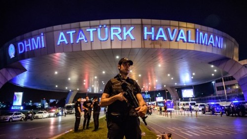 A Turkish riot police officer patrols Ataturk airport`s main entrance in Istanbul, on June 28, 2016, after two explosions followed by gunfire hit Turkey's largest airport. (AFP/ OZAN KOSE)