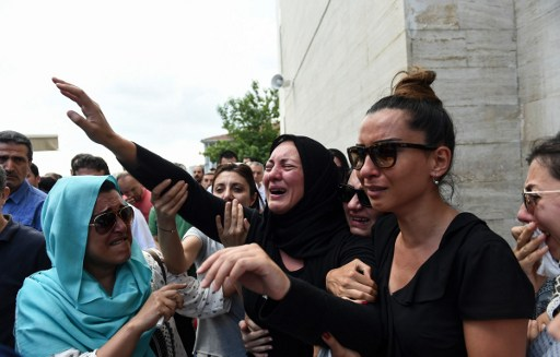 The daughter of Siddik Turgan, who was killed in the June 28, 2016 Istanbul airport attack, reacts as her father's coffin is carried nearby during his funeral ceremony on June 29, 2016. (AFP/BULENT KILIC)